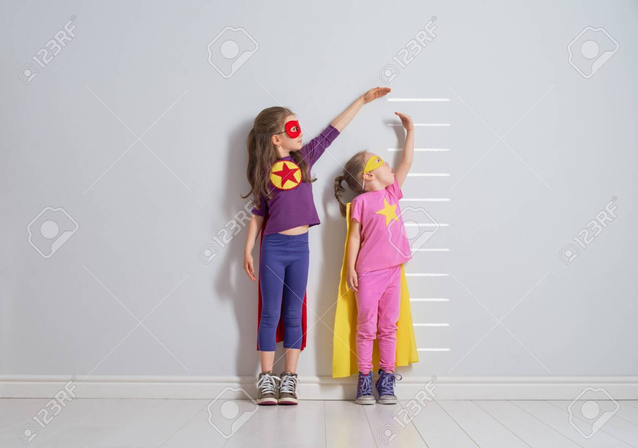 Two little children are playing superhero. Kids are measuring the growth on the background of wall. Girl power concept. - 130556004