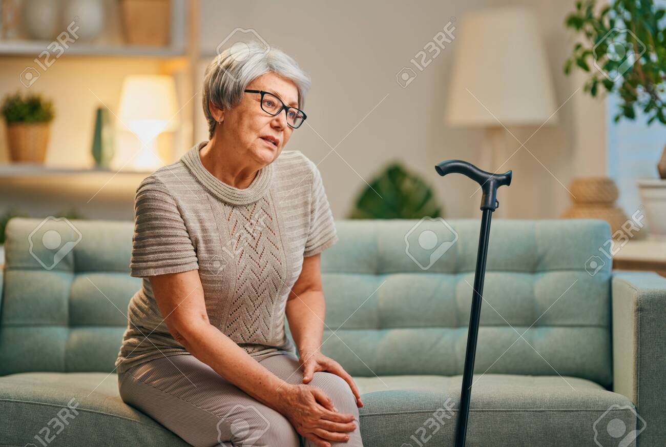 Senior woman with cane. Feeling unwell and pain in the knee. - 135170757