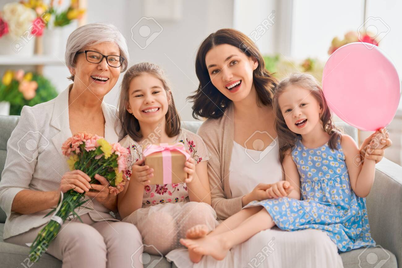 Happy women's day! Children daughters are congratulating mom and granny giving them flowers and gift. Grandma, mum and girls smiling and hugging. Family holiday and togetherness. - 139477678