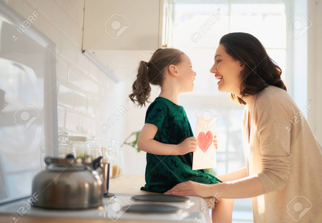 Happy mother's day! Child daughter is congratulating mom and giving her postcard. Mum and girl smiling and hugging. Family holiday and togetherness. - 142557088