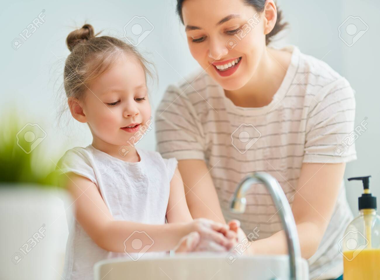 A cute little girl and her mother are washing their hands. - 142932318