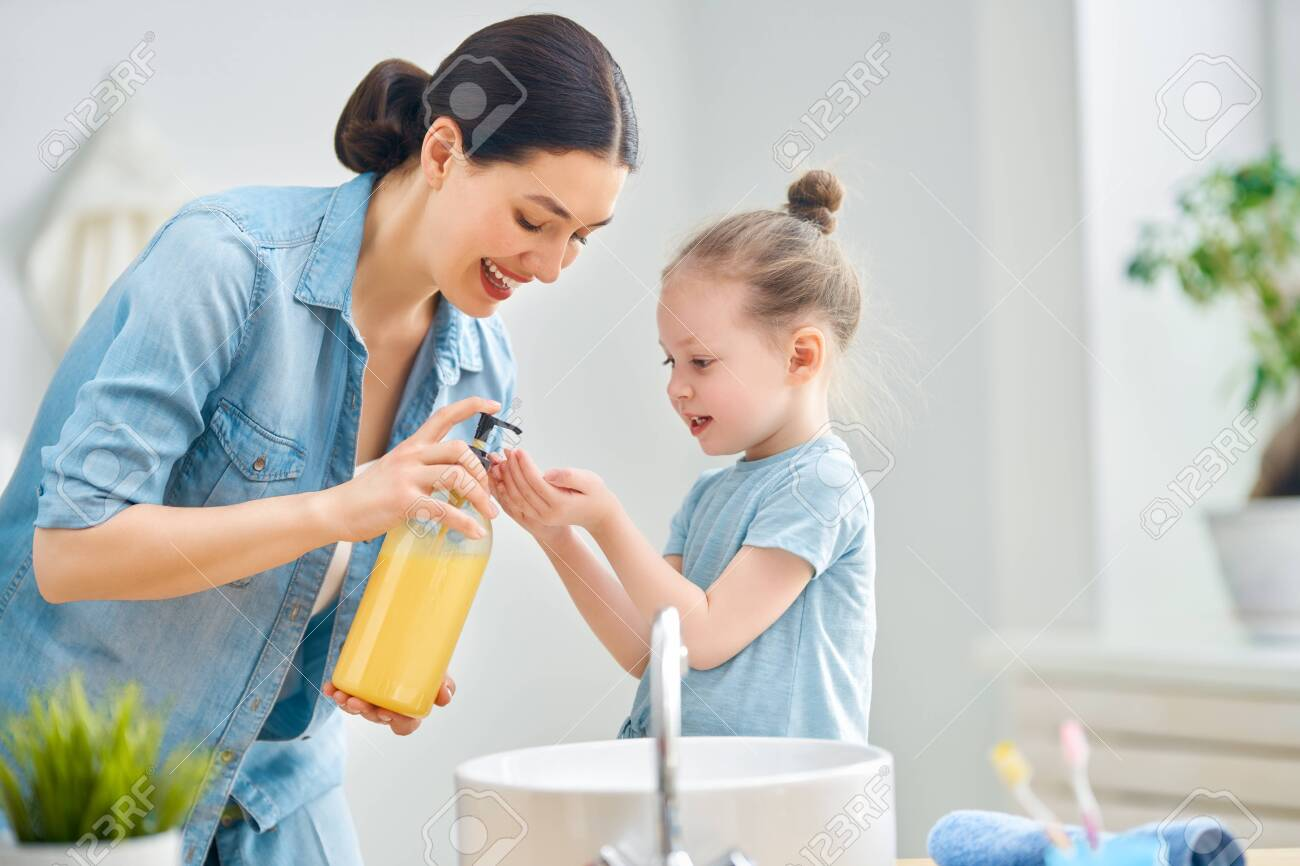 A cute little girl and her mother are washing their hands. - 142932316