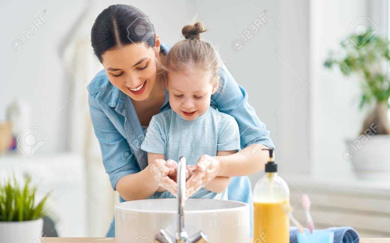 A cute little girl and her mother are washing their hands. - 142932322