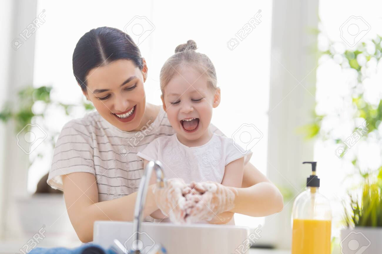 A cute little girl and her mother are washing their hands. Protection against infections and viruses. - 146171438