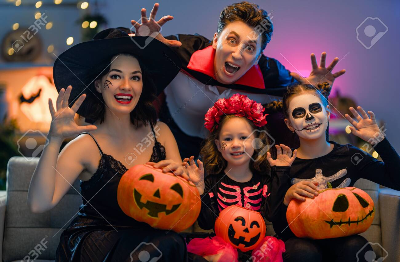 Mother, father and their kids having fun at home. Happy family celebrating Halloween. People wearing carnival costumes and makeup. - 153962476