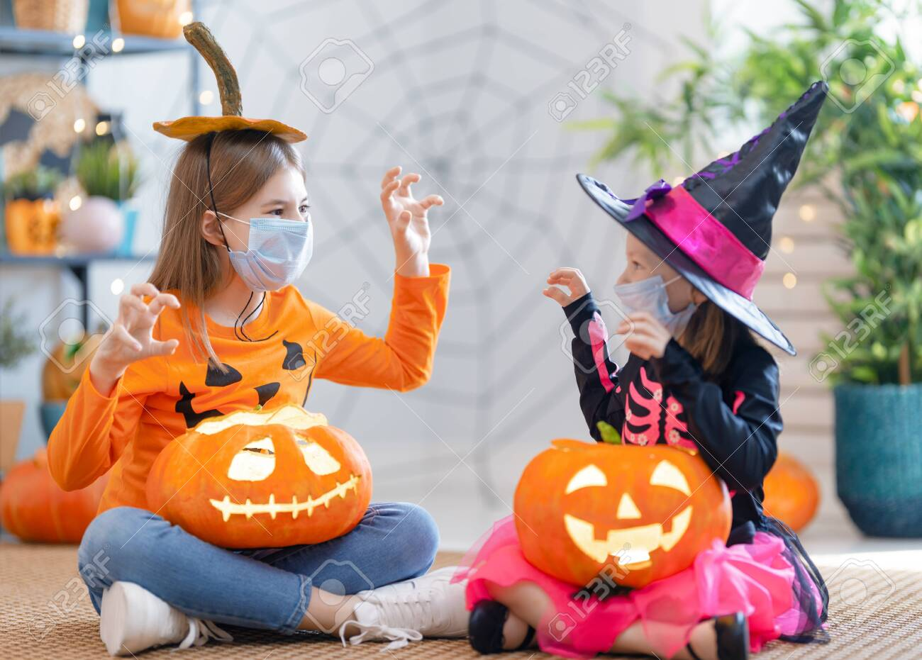 Cute little children girls in carnival costumes wearing face masks. Happy family preparing for Halloween protecting from COVID-19. - 156114773
