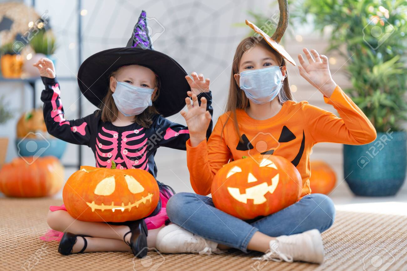 Cute little children girls in carnival costumes wearing face masks. Happy family preparing for Halloween protecting from COVID-19. - 156610550