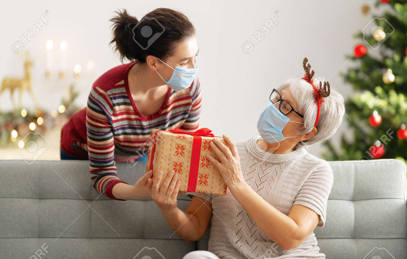 People with gifts wearing facemasks during coronavirus and flu outbreak on Christmas. Virus and illness protection, home quarantine. COVID-2019 - 158744134