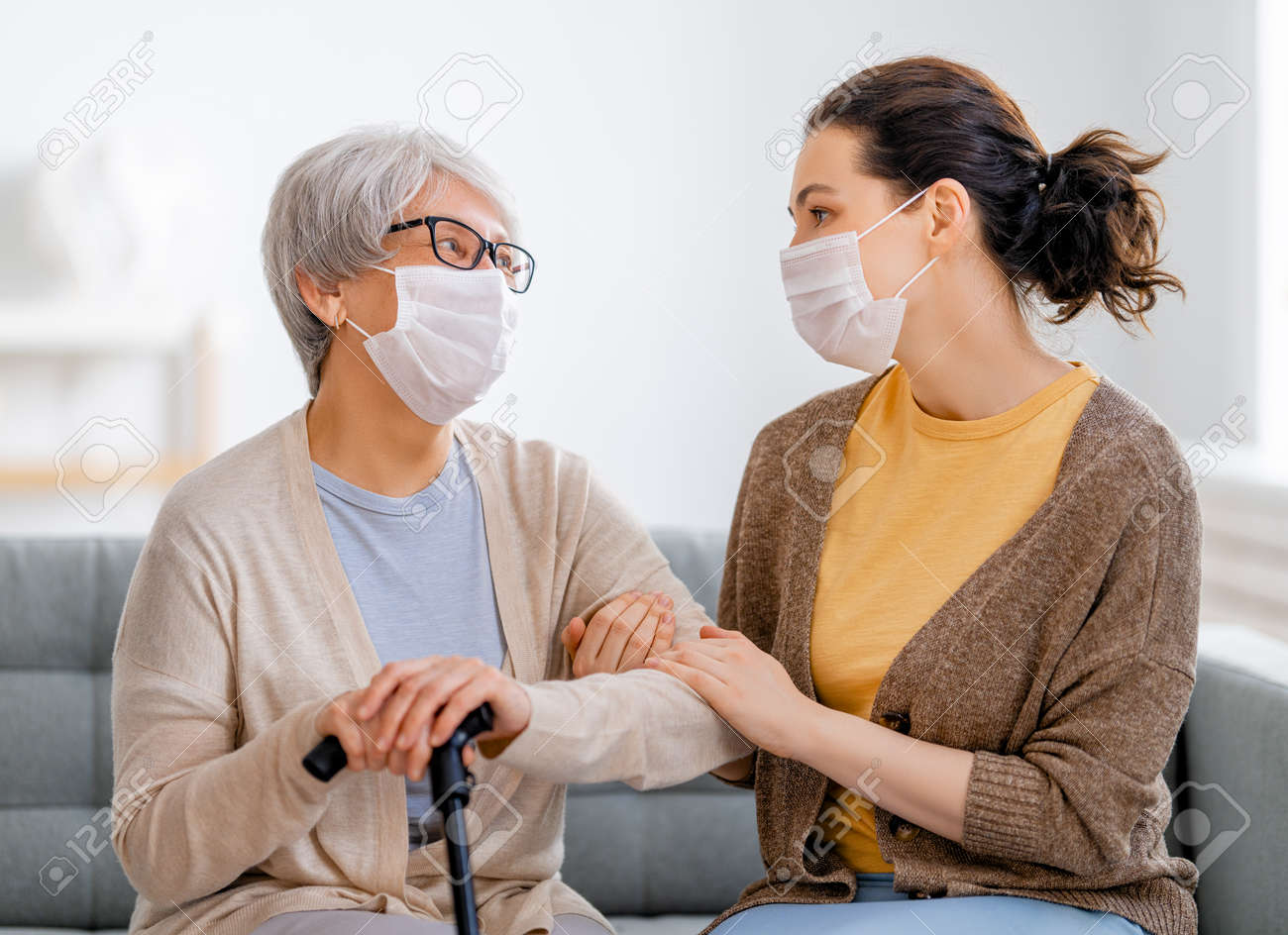 Adult daughter and senior parent wearing facemasks during flu outbreak. Help for the convalescent. - 164058189