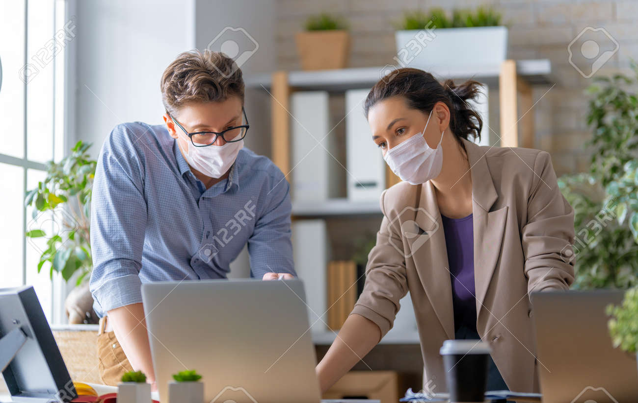Businessman and businesswoman with medical mask working in office. Covid-19 time. - 164417495
