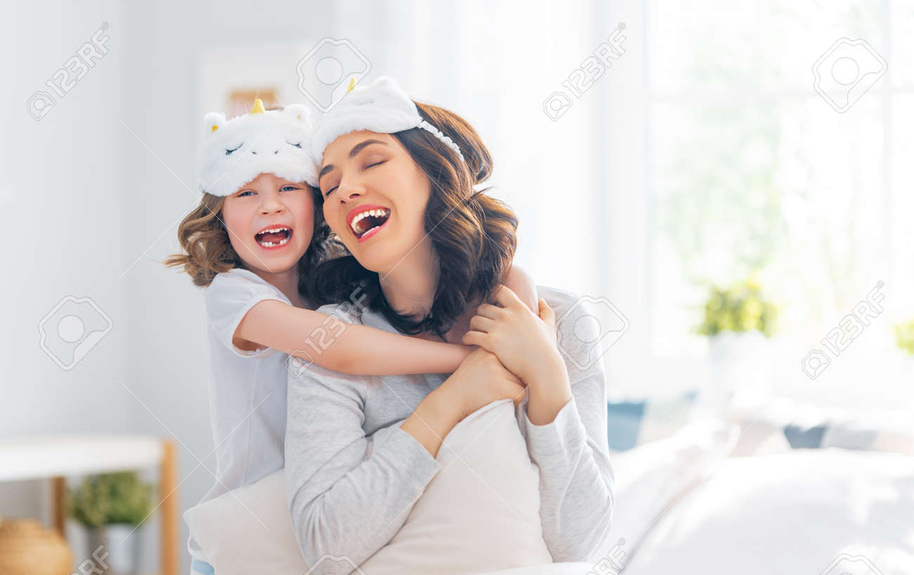 A nice girl and her mother enjoying sunny morning. Good time at home. Child wakes up from sleep. Family playing on the bed in the bedroom. - 168325237