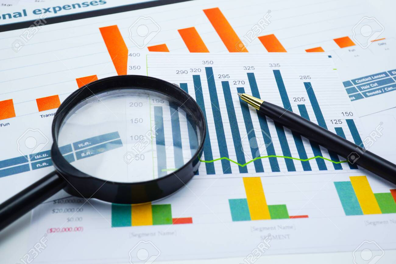 Magnifying glass on charts graphs spreadsheet paper. Financial development, Banking Account, Statistics, Investment Analytic research data economy, Stock exchange trading, Business office company meeting concept. - 130343582
