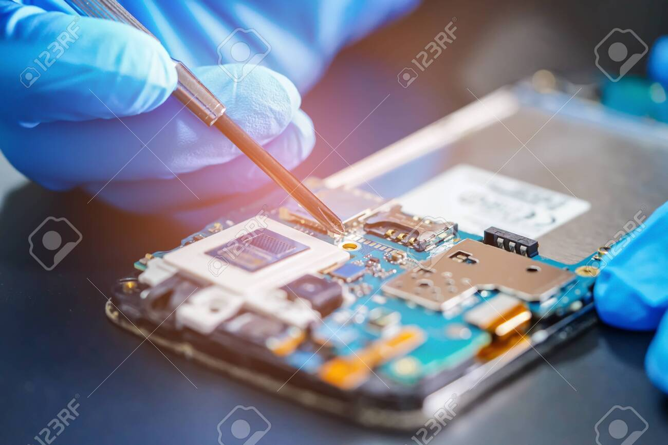 Asian Technician repairing micro circuit main board of smartphone electronic technology : computer, hardware, mobile phone, upgrade, cleaning concept. - 130353498