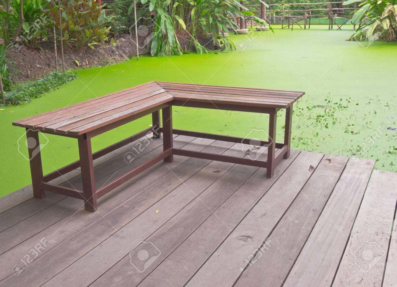 Derecha Banco De Madera ángulo En La Terraza Al Lado De La Charca Verde De La Lenteja De Agua