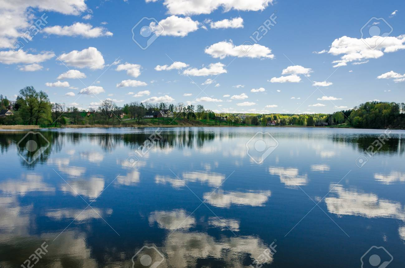 Cloudy blue sky reflects into the lake with trees on the horizon. - 77455849