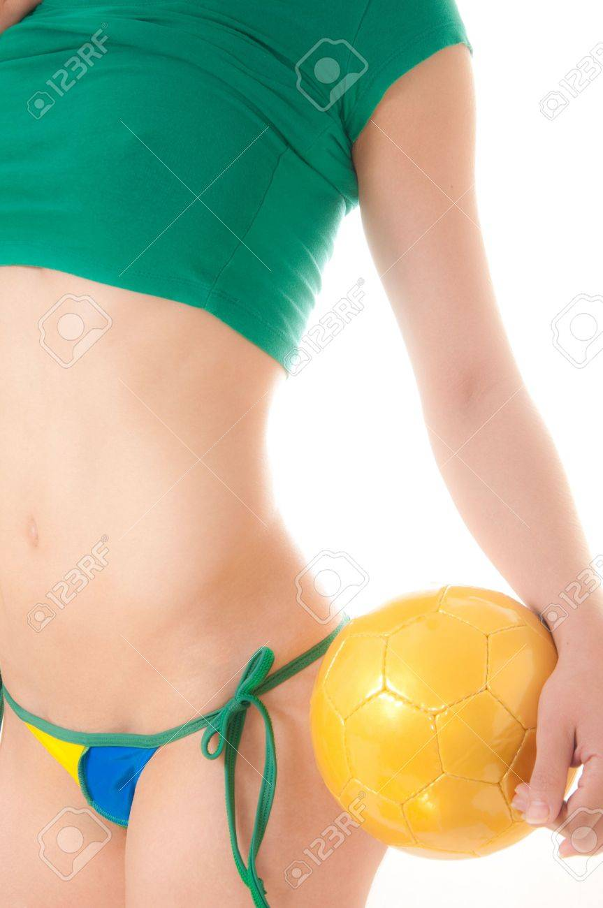 Beautiful Brazilian model wearing a green and yellow soccer thong bikini bottom  holding a soccer ball isolated over white background Stock Photo - 8264865
