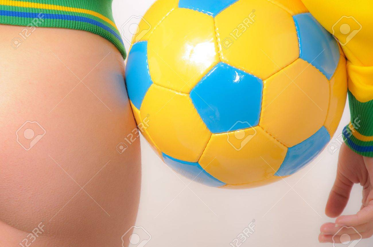 Beautiful Brazilian model wearing a green and yellow soccer thong bikini bottom  holding a soccer ball isolated over white background Stock Photo - 8264861