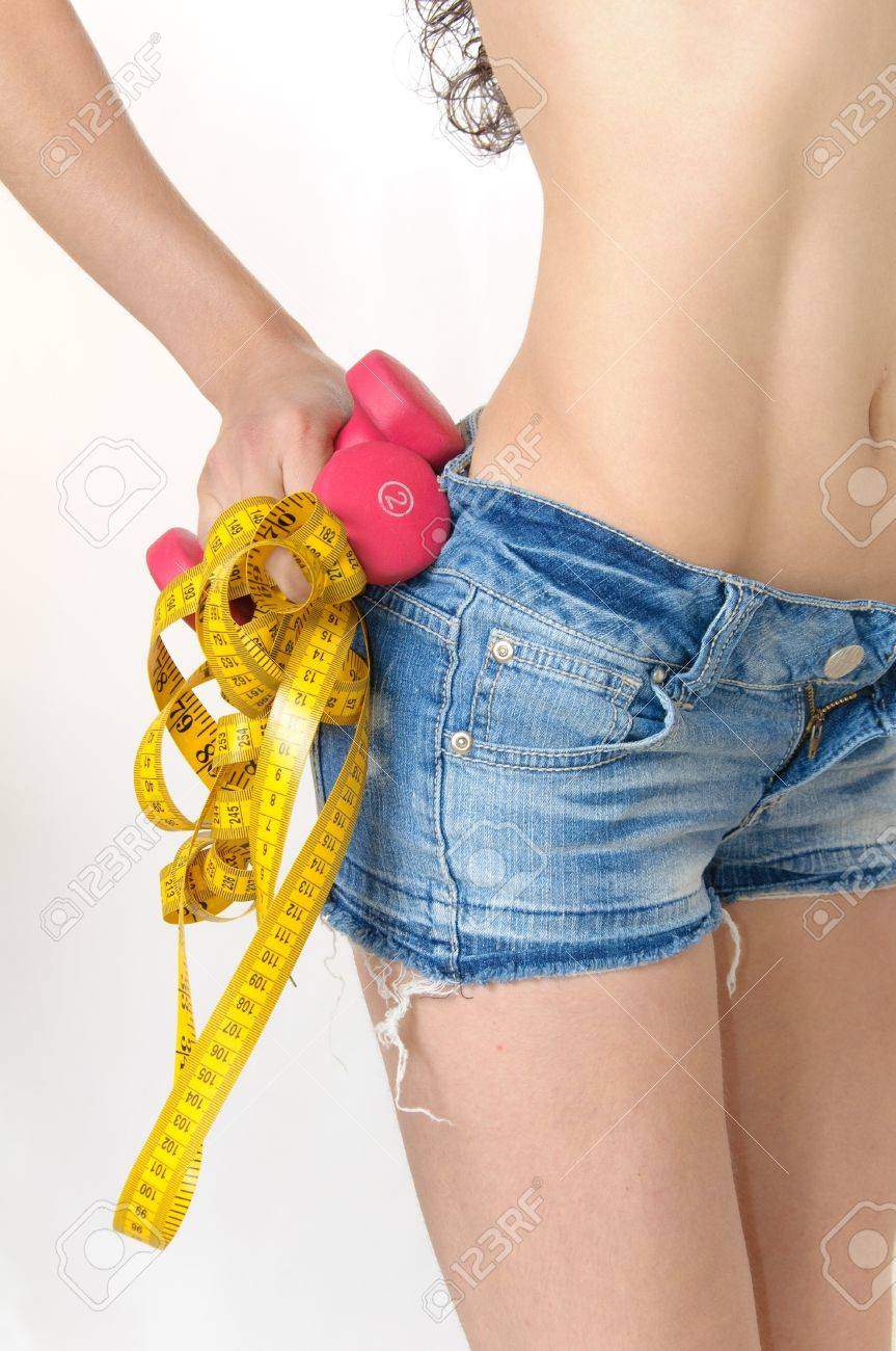 Model wearing blue jeans shorts holding a yellow measuring tape and red dumbells Stock Photo - 8264883