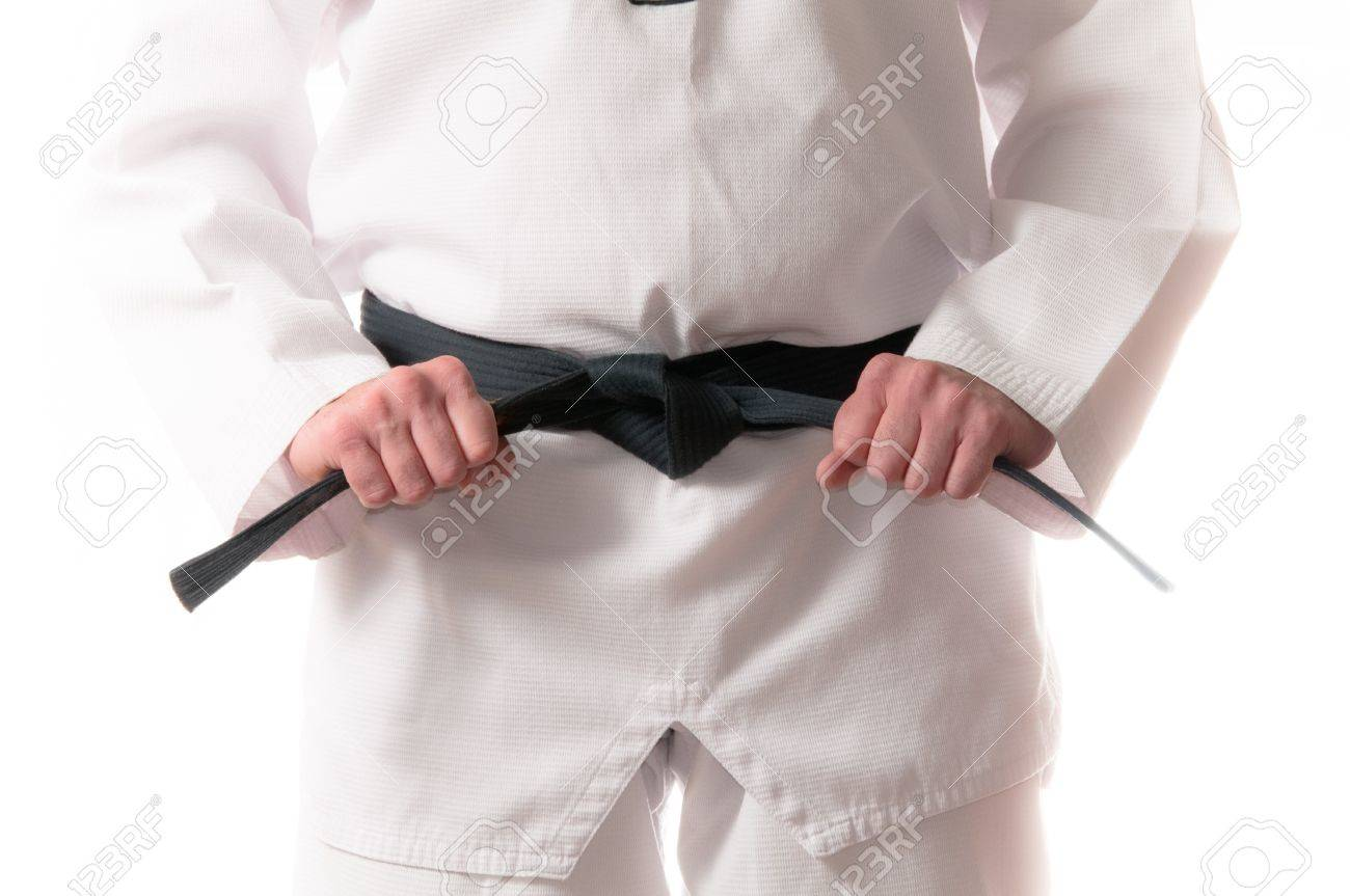Man in martial arts uniform holding his black belt with both hands Stock Photo - 8264857