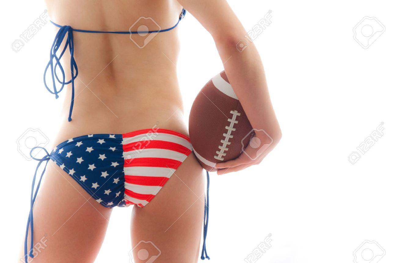 Beautiful woman wearing the United States flag bikini holding a football isolated over white background Stock Photo - 8609347