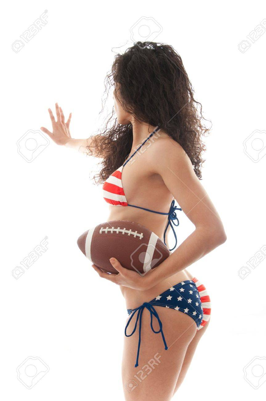 Beautiful woman wearing the United States flag bikini holding a football isolated over white background Stock Photo - 8609351