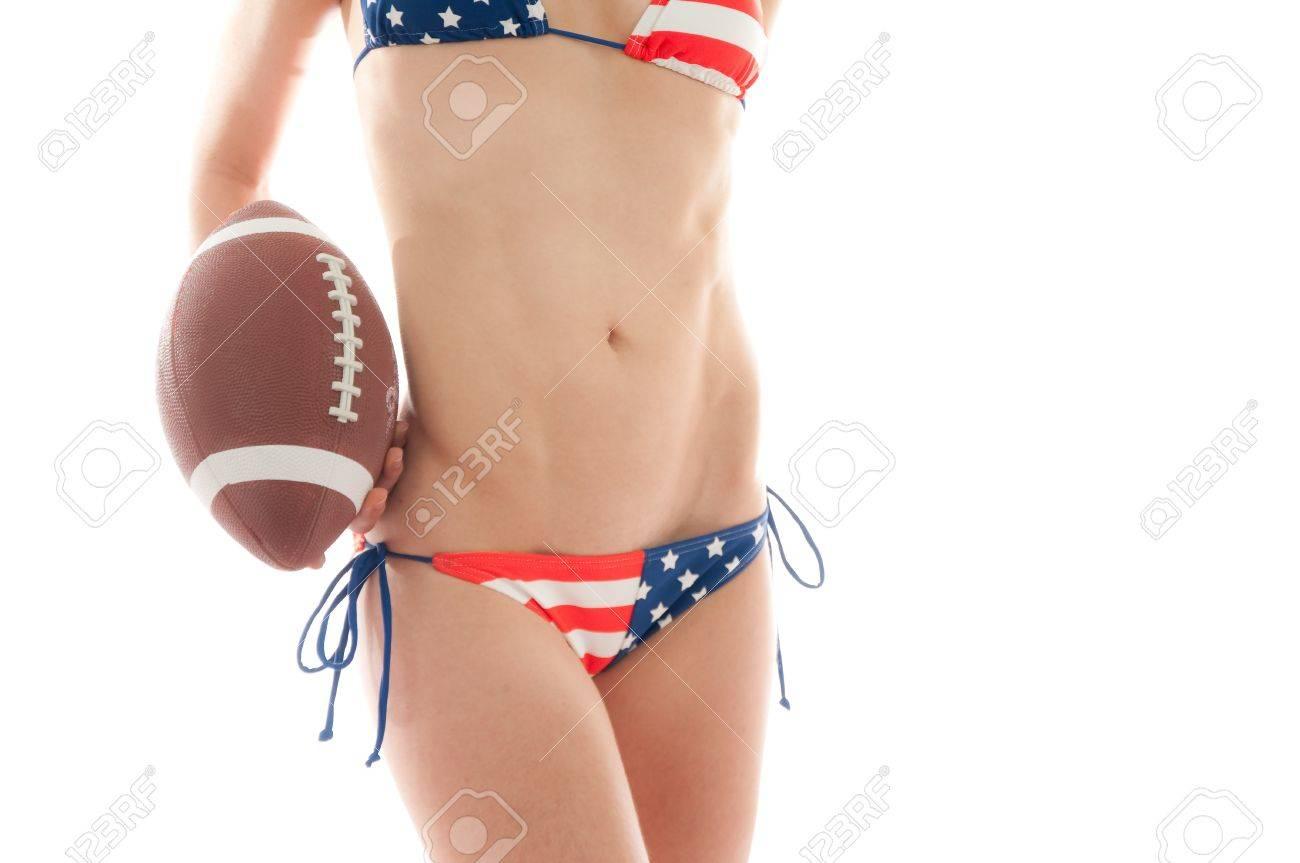 Beautiful woman wearing the United States flag bikini holding a football isolated over white background Stock Photo - 8709999