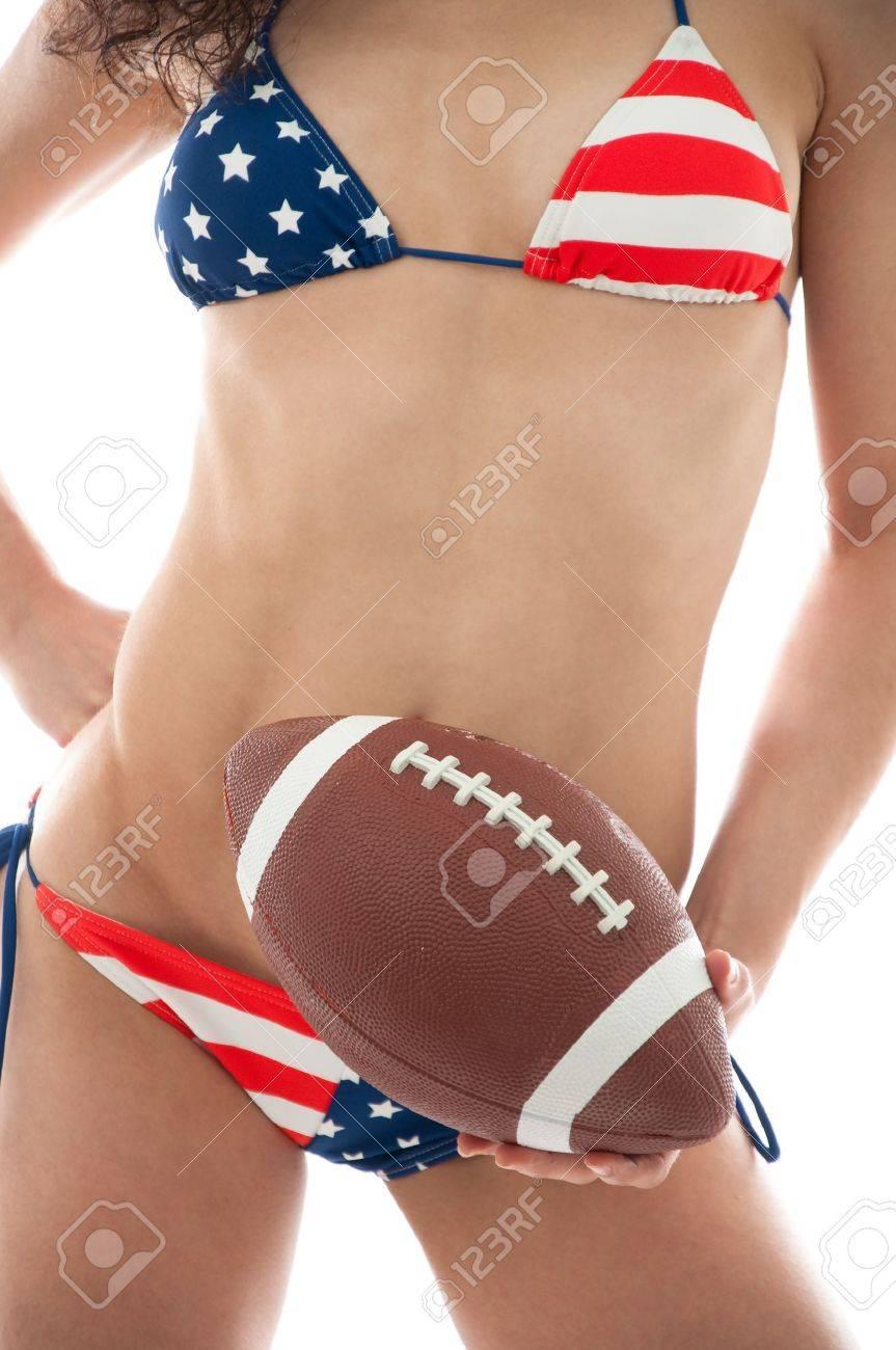 Beautiful woman wearing the United States flag bikini holding a football isolated over white background Stock Photo - 8710007