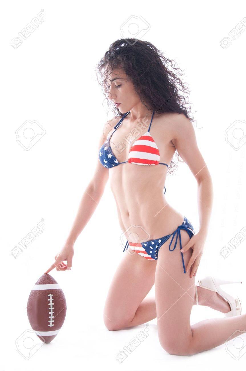 Beautiful woman wearing the United States flag bikini holding a football isolated over white background Stock Photo - 14790334