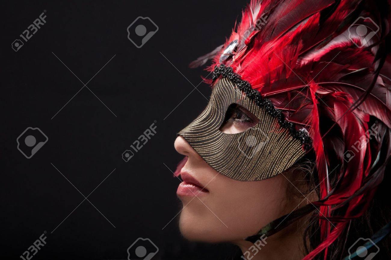 Beautiful model wearing a feather mask symbolizing mardi gras or venetian carnival Stock Photo - 14790377