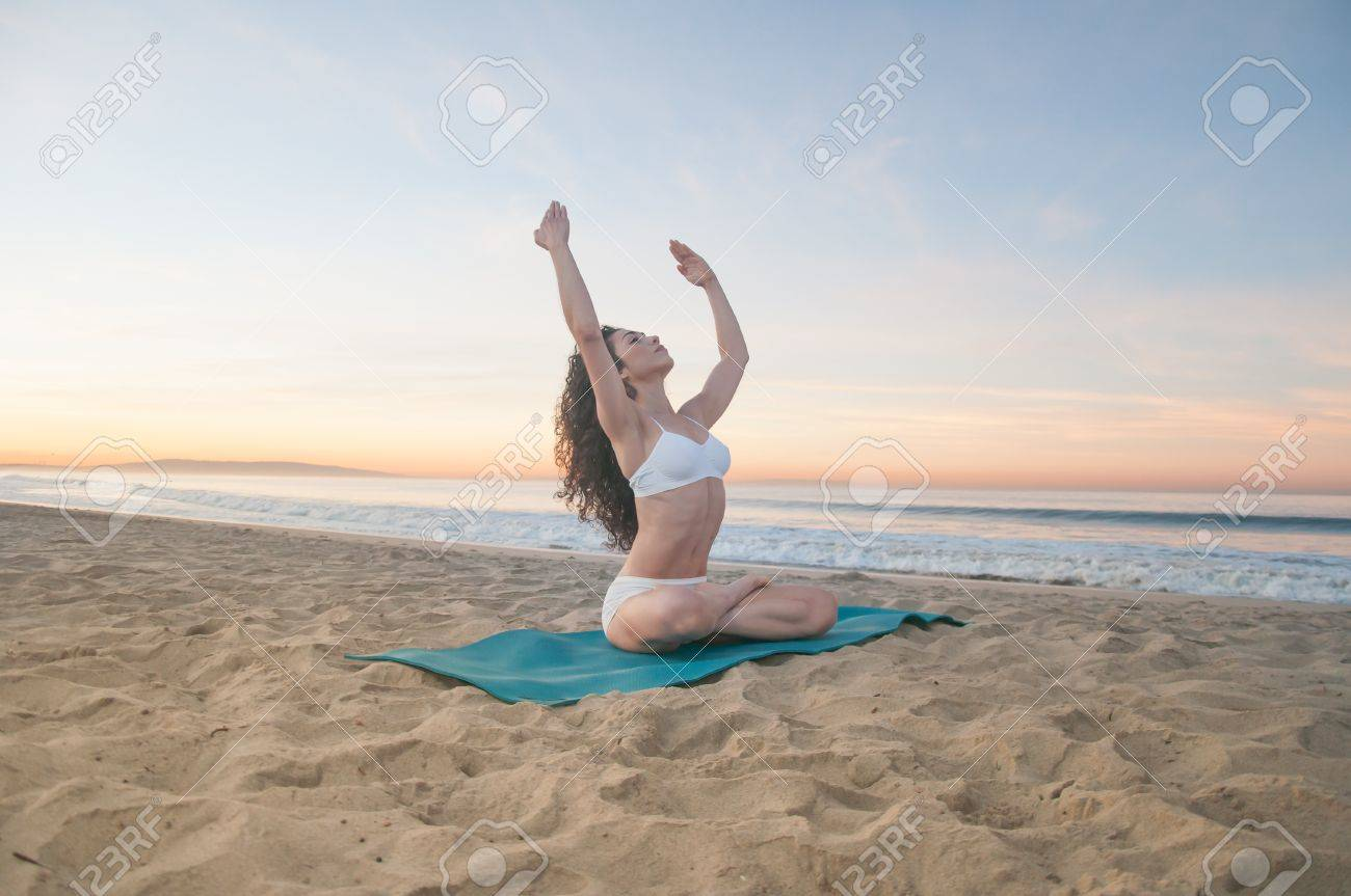 Beautiful athletic woman praticing energizing and relaxing yoga exercises on a colorful sunrise on the beach Stock Photo - 16249036