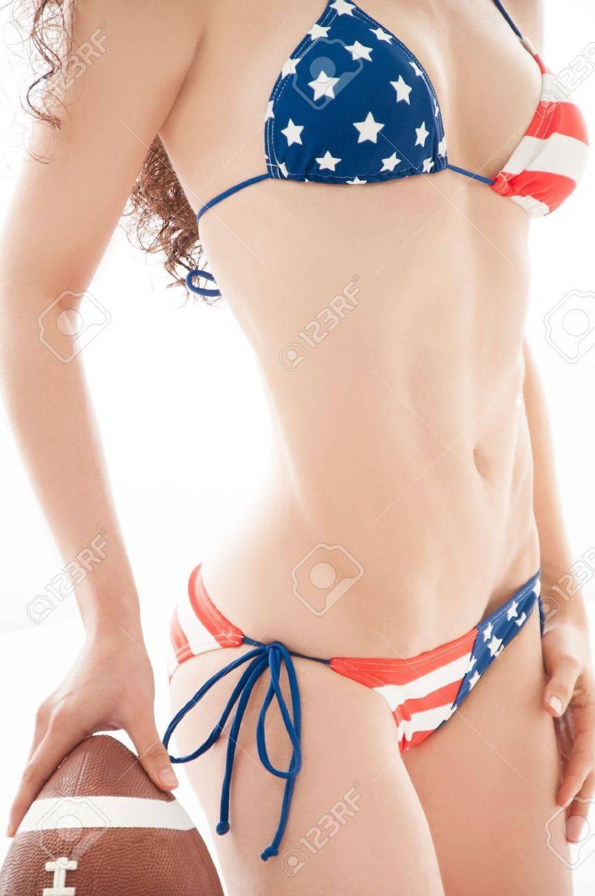 Beautiful woman wearing the United States flag bikini holding a football isolated over white background Stock Photo - 17055853