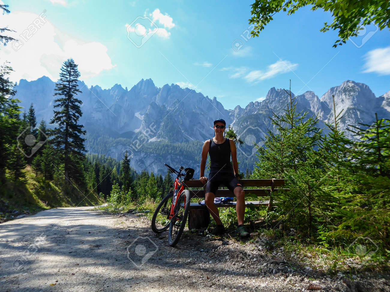 A man in biking outfit standing next to orange mountain bike next to a gravelled road in the mountains with the view on high Alps in the region of Gosau, Austria. Stony and barren mountain chains. - 167652718