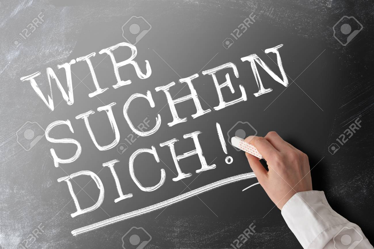hand holding piece of chalk writing words WIR SUCHEN DICH, German for we are looking for you or we want you, job offer and opportunity concept - 123379369