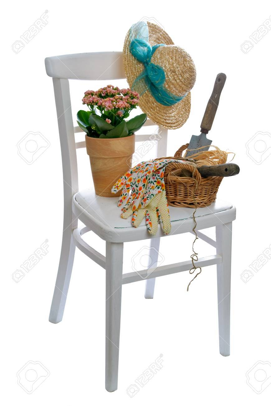 Rustic white chair laden with garden tools and straw hat Stock Photo - 4739928