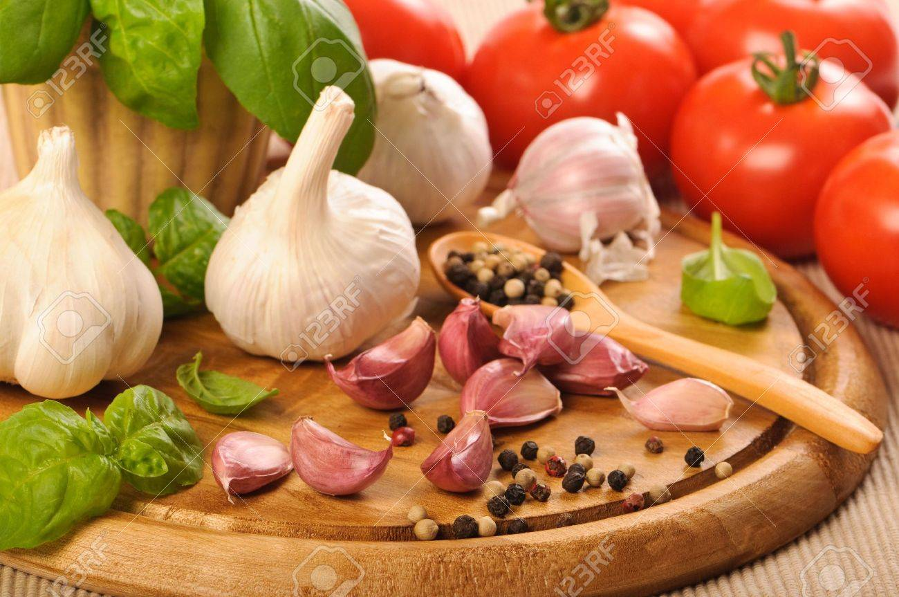 Garlic bulbs and cloves with basil on wooden chopping board with tomatoes in background Stock Photo - 5430501