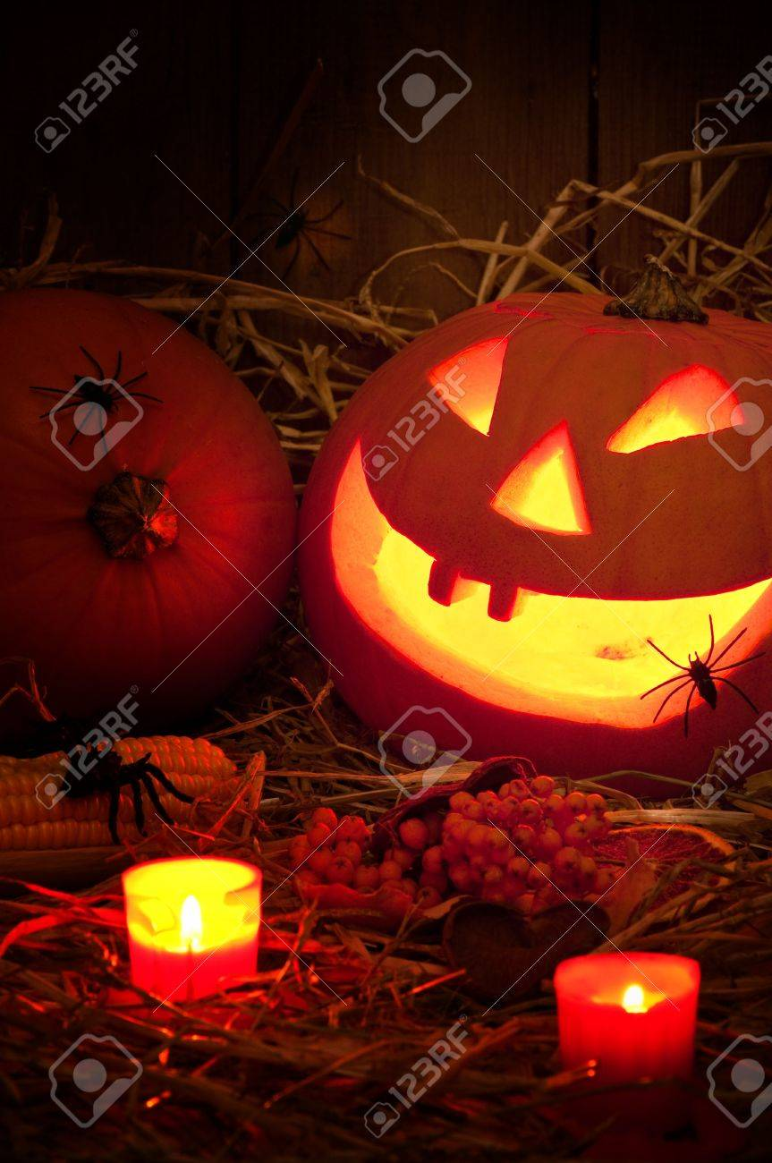 spooky halloween pumpkin with lit candles in the barn with spiders crawling in the straw stock - Halloween Barn