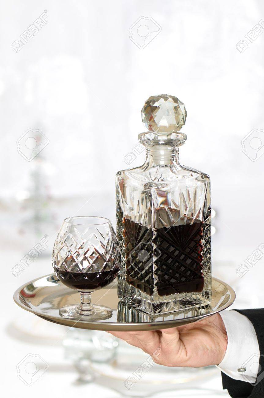 waiter serving brandy to dining table decorated for christmas