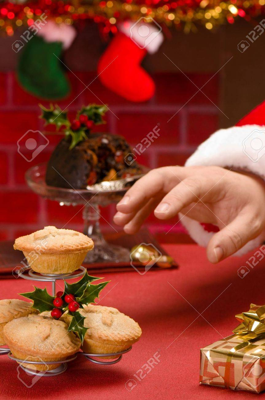 Santa Claus on Christmas eve reaching for a mince pie Stock Photo - 5806351