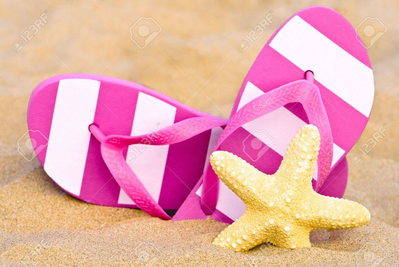 532465b1a480 Stock Photo - Summer flip flops on the beach with starfish