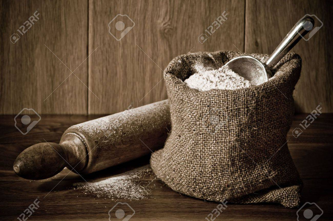 Wholemeal wheat flour in burlap sack with antique rolling pin Stock Photo - 6648109