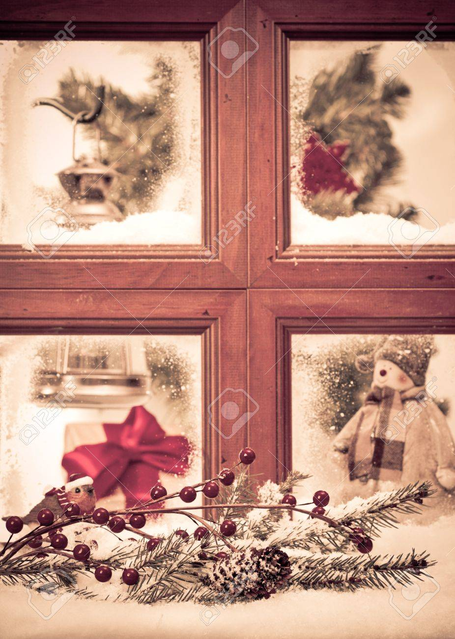 Vintage Christmas window with snowy scene, focus on fir cone and branch in front of window Stock Photo - 11151174
