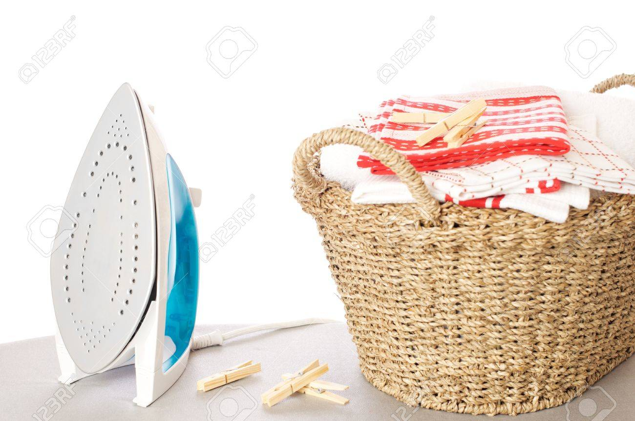 Basket of freshly laundered washing in basket with iron and clothes pegs Stock Photo - 12128395