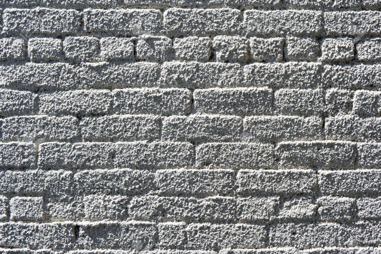 A brick wall sprayed with white stucco