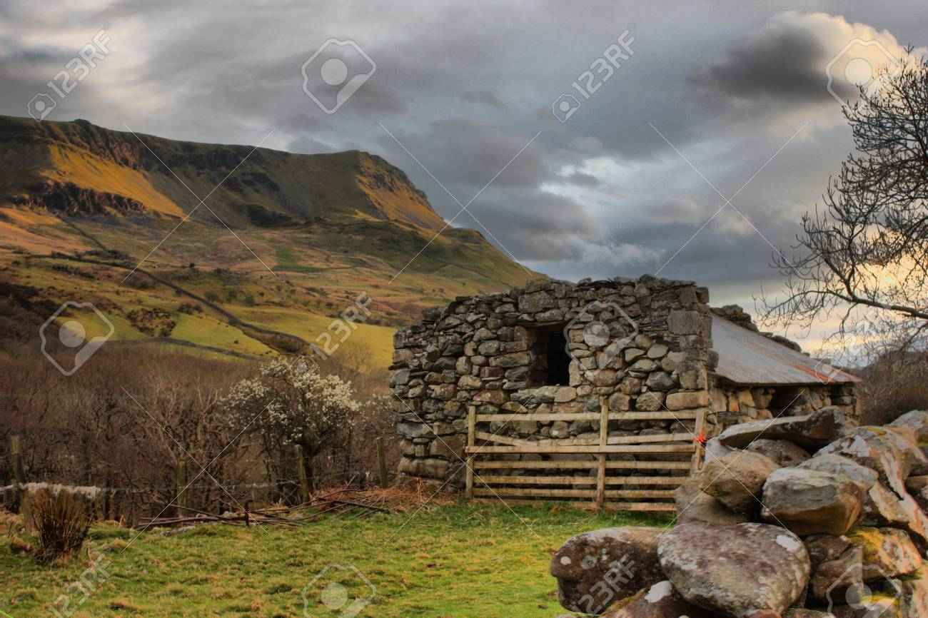 a disused barn in front of a moody sky over a mountain Stock Photo - 13219126