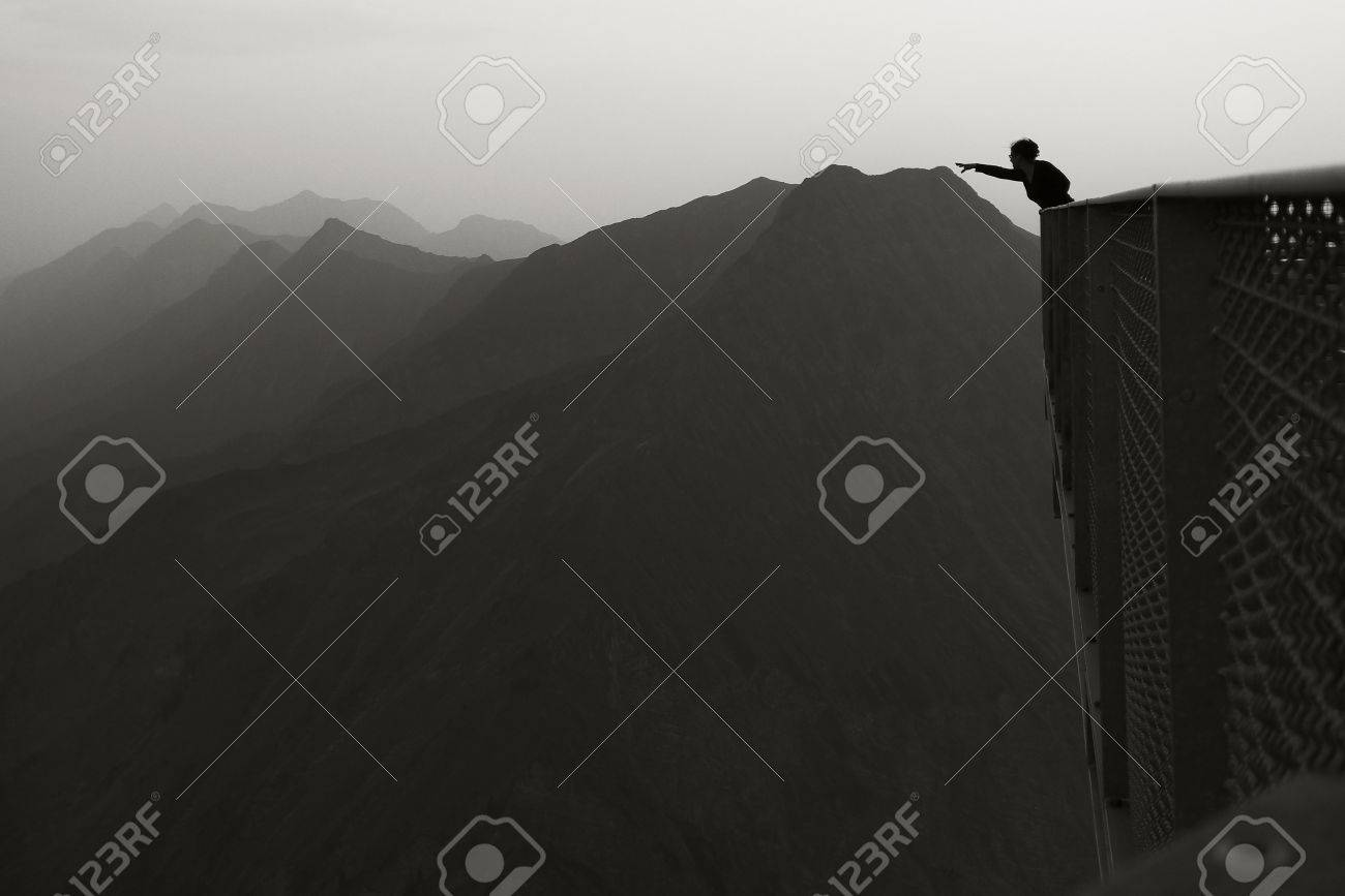 Reaching the mountains - A person in the foreground stretching out here arm to a fare away mountain range. Stock Photo - 50157389
