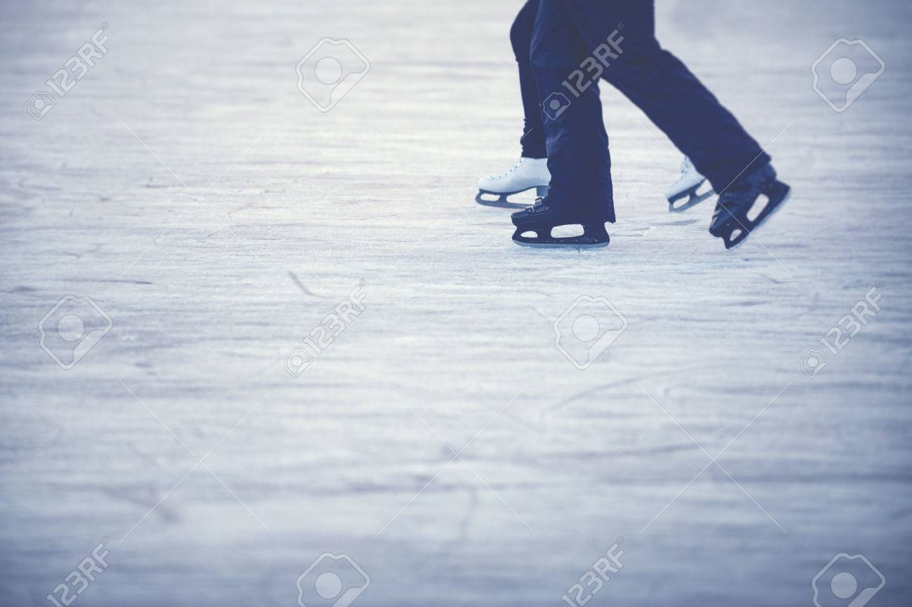 Ice skating couple - Legs of woman and man with white and black skates. Stock Photo - 50157397
