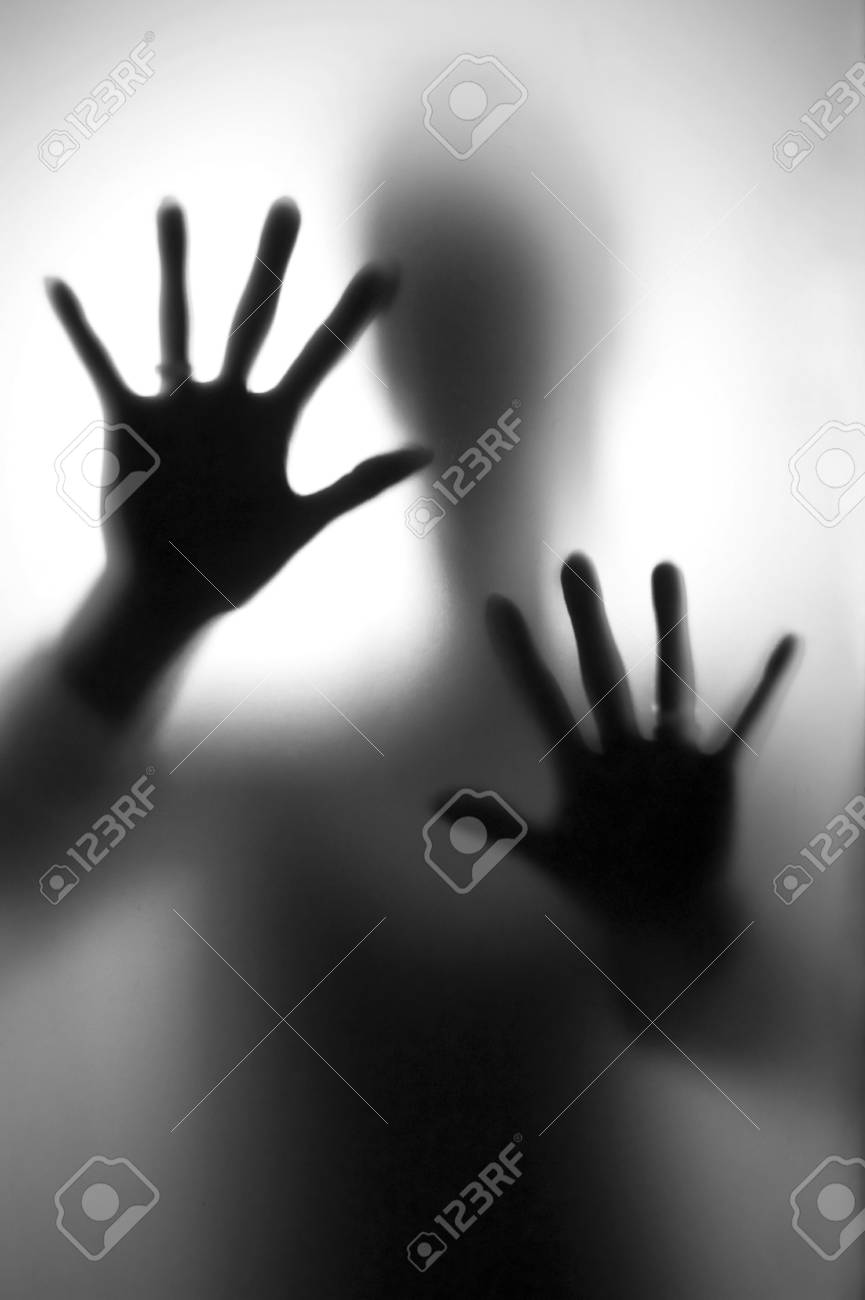 Person in fear - Silhouette of a woman, defending her self with here hands. Stock Photo - 50157396