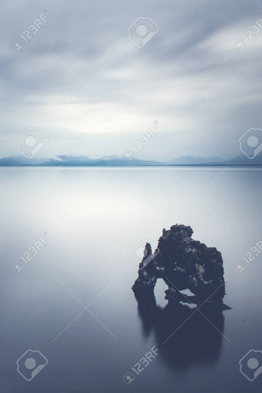Rock in the calm sea - The Servitude rock in Iceland is a impressive landmark. Legend has it that it is a troll. Stock Photo - 50157400