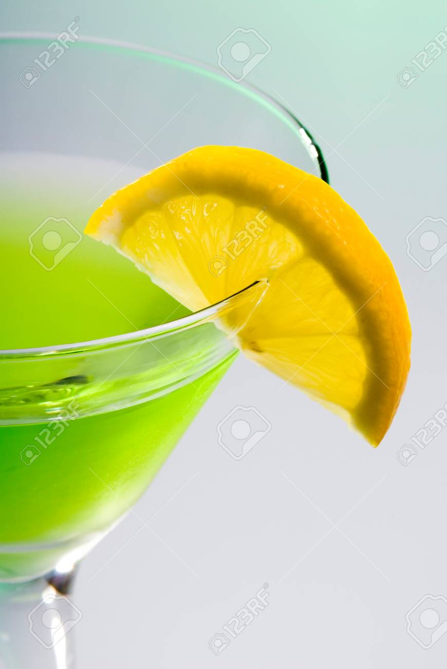 this image shows a lemon slice on a green martini