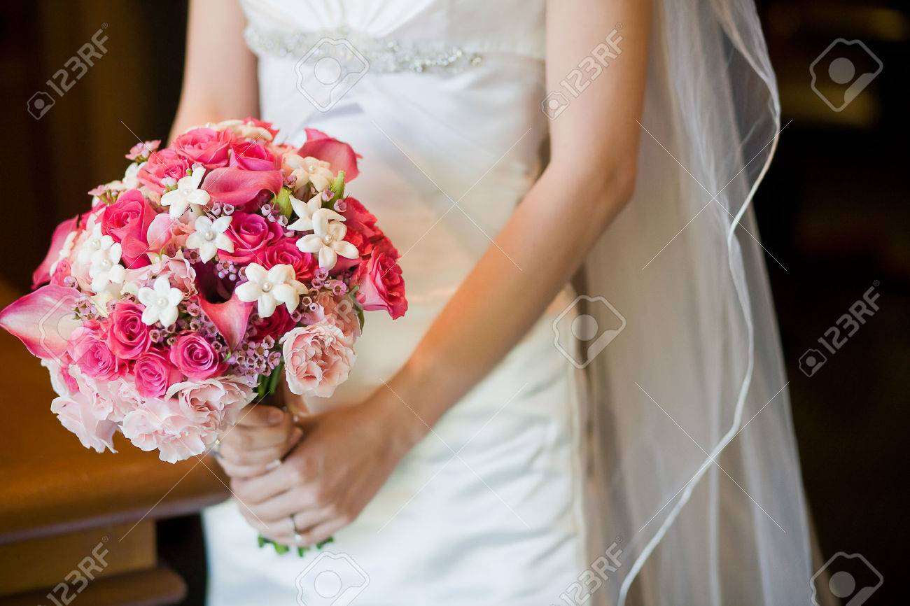 Bride holding beautiful wedding bouquet consisting of light pink bride holding beautiful wedding bouquet consisting of light pink roses hot pink roses pink mightylinksfo Gallery